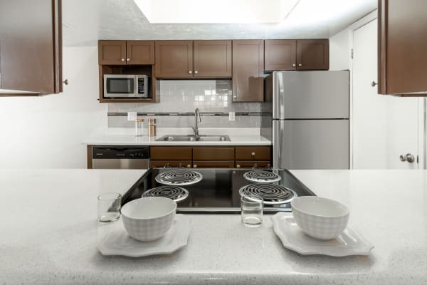 Brown Renovated Kitchen with stainless steel appliances at at Windgate Apartments in Bountiful, Utah