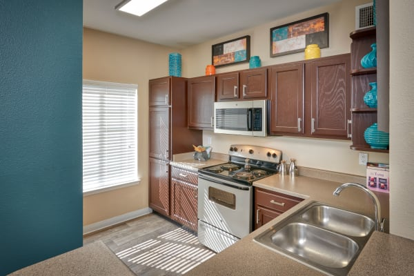 Renovated brown cabinetry model kitchen at Skyecrest Apartments in Lakewood