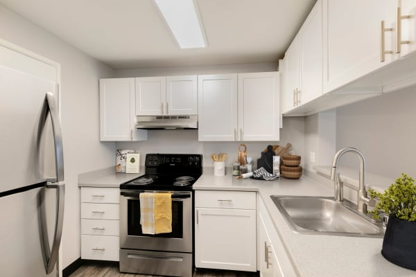 White renovated kitchen with stainless steel appliances at Meadows at Cascade Park Apartments in Vancouver