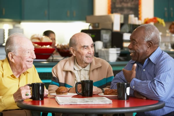 Three gentlemen sit at a table and enjoy a coffee chat at First & Main of Auburn Hills in Auburn Hills, Michigan