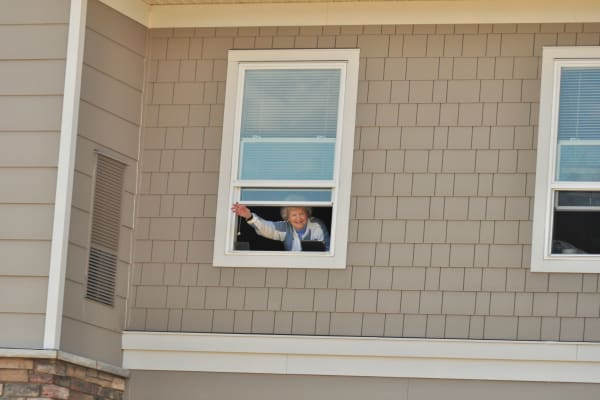 Resident waving out of her window at Deephaven Woods in Deephaven, Minnesota