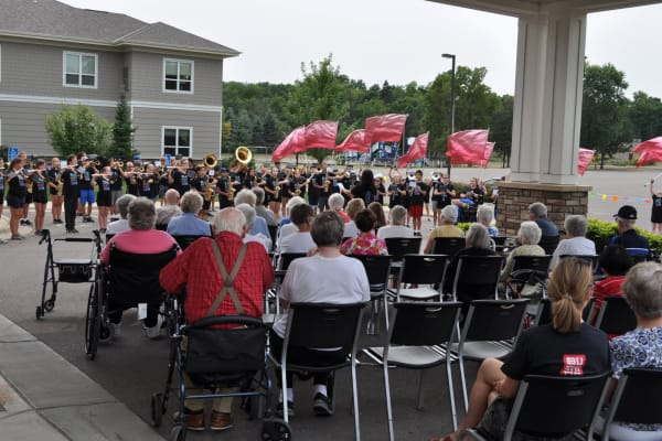 Residents gathered to watch a marching band play at Deephaven Woods in Deephaven, Minnesota