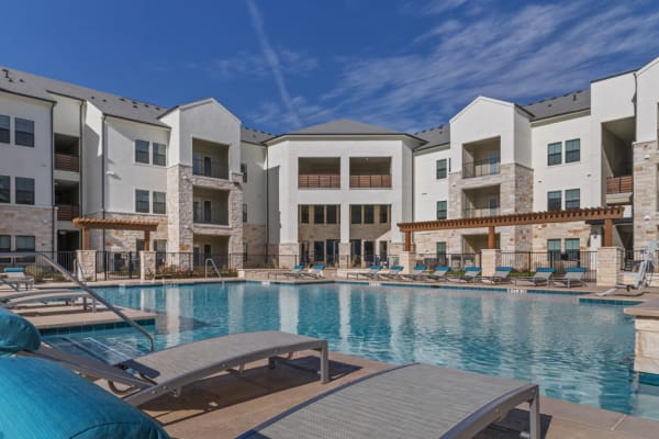 Swimming pool with a large sundeck at McCarty Commons in San Marcos, TX
