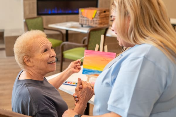 Resident and staff member at Seasons Memory Care at Rolling Hills in Torrance, California.