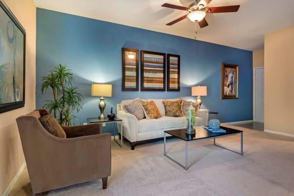 Model living room with plush carpeting and ceiling fan at Foundations at River Crest & Lions Head in Sugar Land, Texas