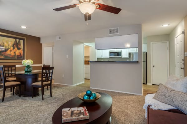 Living room and dining area with pass-through to the kitchen in an open layout model apartment home at Foundations at Edgewater in Sugar Land, Texas