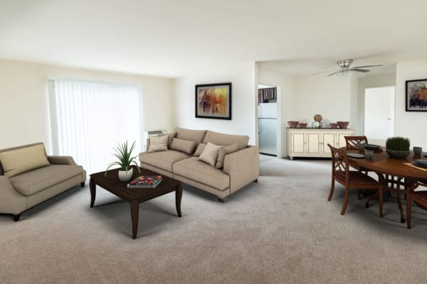 Spacious living room and dining area with plush carpeting in a model apartment home at Brakeley Gardens in Phillipsburg, New Jersey