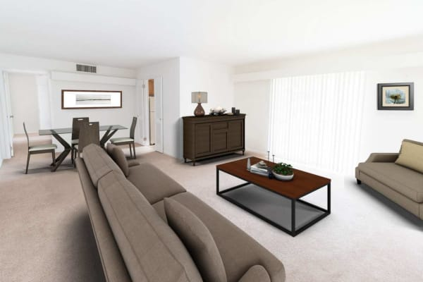 Spacious living room and dining area with plush carpeting in a model apartment home at Corliss Apartments in Phillipsburg, New Jersey