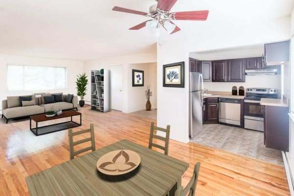 Spacious living room and dining area with hardwood floors and a ceiling fan in an open floorplan model apartment home at Laurel Run Village in Bordentown, New Jersey