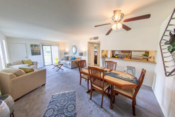Spacious living room and dining area with plush carpeting and a ceiling fan in a model apartment home at Forest Creek in West Deptford, New Jersey