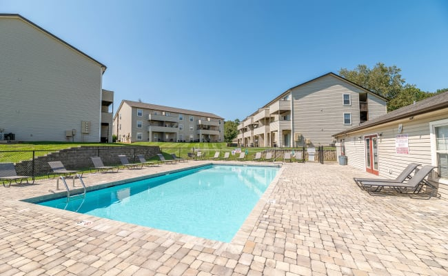 Beautiful swimming pool with a brick sundeck at Kannan Station Apartment Homes in Kannapolis, North Carolina