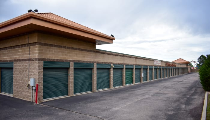 Green exterior storage unit doors and a wide driveway at a STOR-N-LOCK Self Storage location