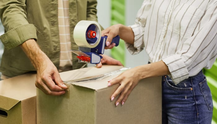 Two people sealing a box with packing tape at A Storage Place