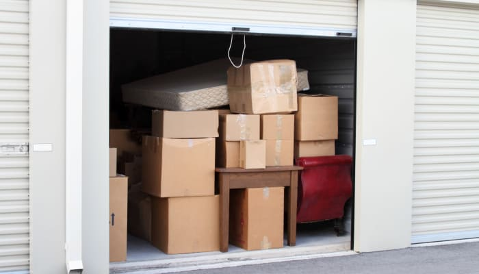 A woman holding a tablet and a man loading boxes into a storage locker at A Storage Place in Tualatin, Oregon