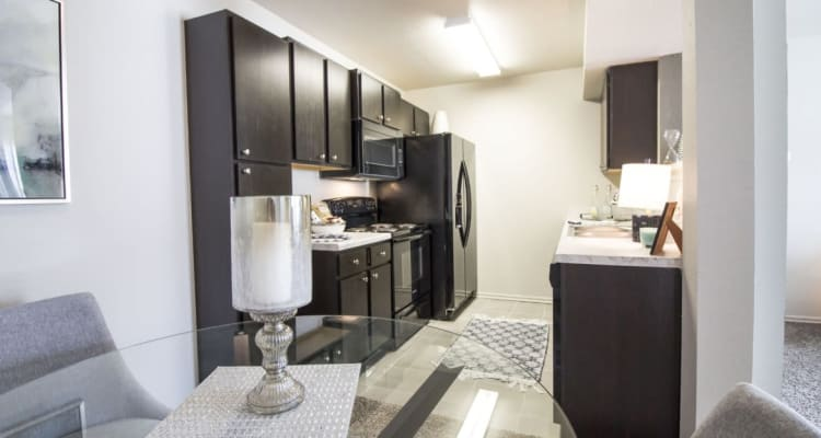 A kitchen and dining room in a model apartment at Legacy Trail in Norman, Oklahoma