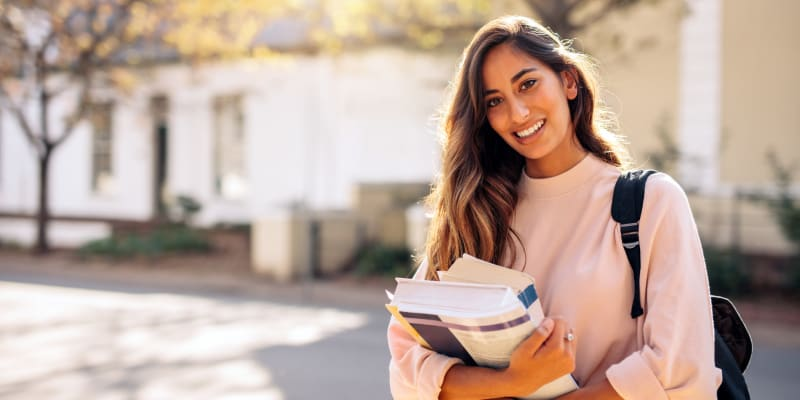 College student holding her books near Harbor Group Management in Norfolk, Virginia