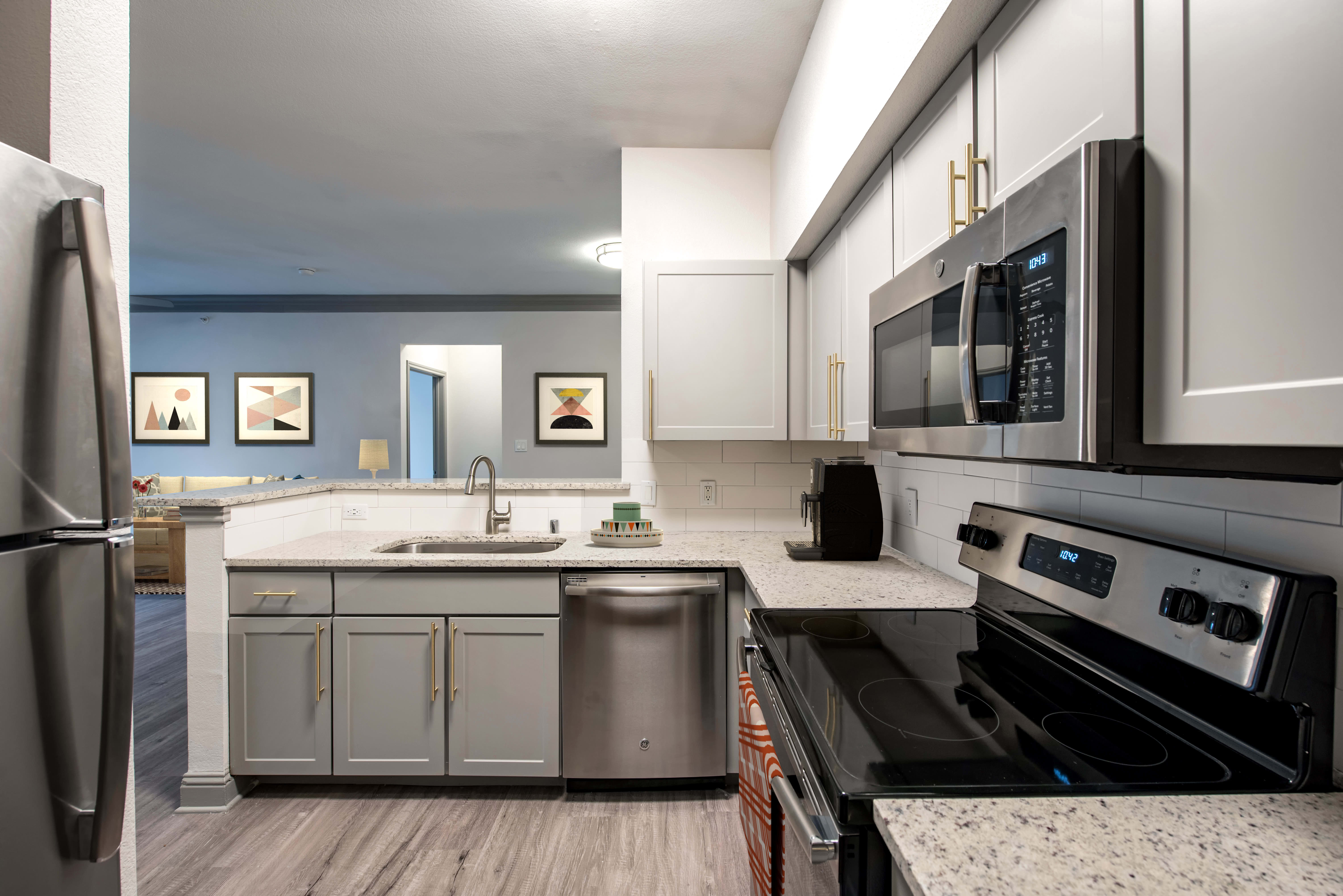 Spacious and modern kitchen in model home at Abbey at Vista Ridge Apartments in Lewisville