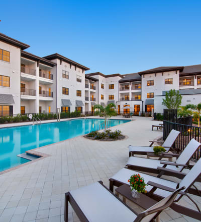 Outdoor seating by the pool at Keystone Place at Naples Preserve in Naples, Florida