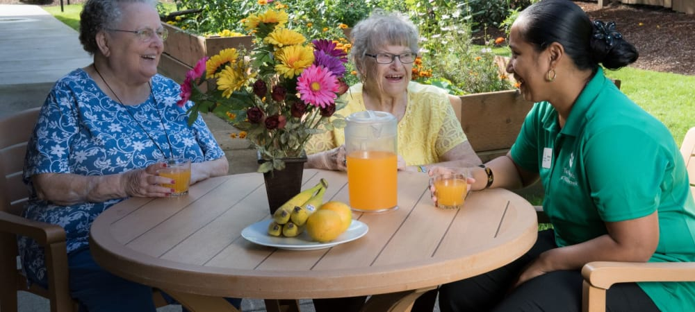 Two residents enjoying a beverage with an employee at an upscale senior living facility at a table outside on a sunny day at The Springs at Willowcreek in Salem, Oregon