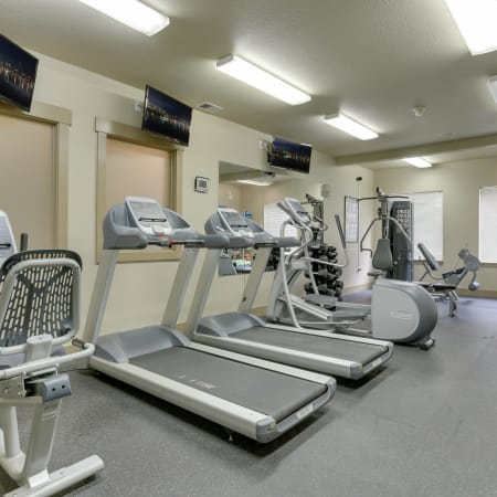 newly renovated fitness center with cardio machines and TVs