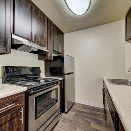 Brown Renovated Kitchen Room with stainless steel appliances at The Timbers Apartments in Hayward