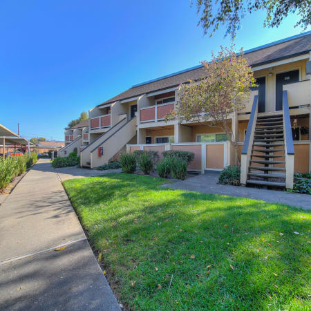 Exterior Building and Walkway shot with green space of The Timbers Apartments in Hayward