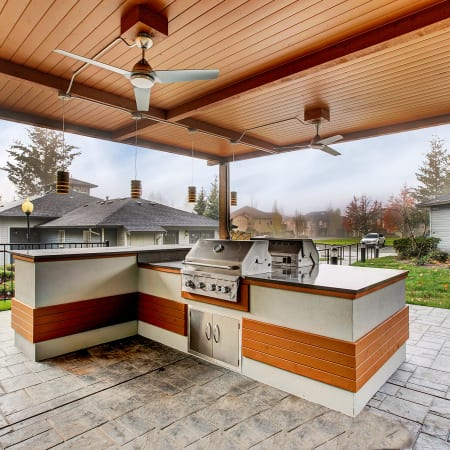 Covered Outdoor BBQ with bar top seating at Pebble Cove Apartments in Renton