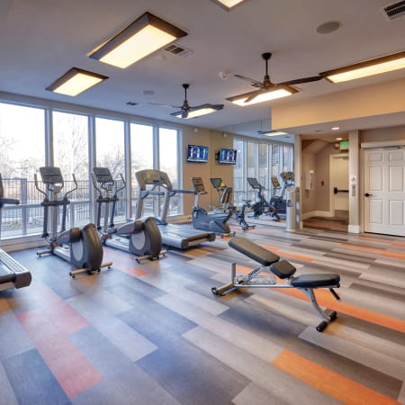 fitness center with large windows at The Crossings at Bear Creek Apartments