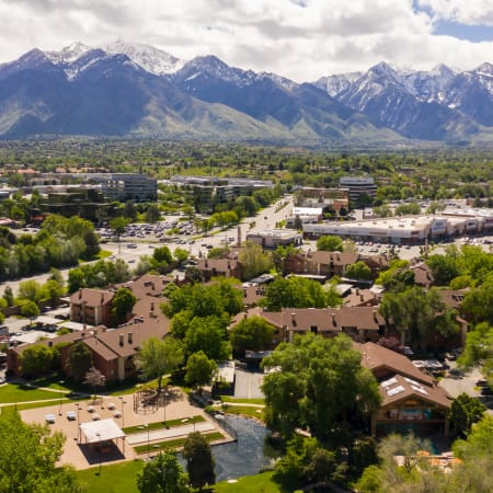 Aerial view of property and surrounding areas and mountain int he background of Springs of Country Woods Apartments in Midvale