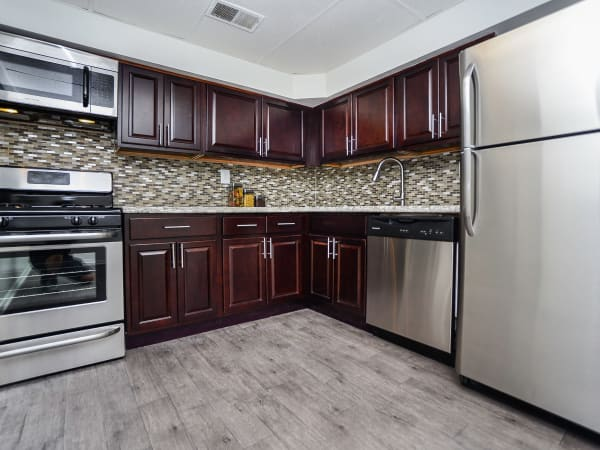 Fully equipped kitchen with dark wooden cabinetry at Willowbrook Apartment Homes in Baltimore, MD