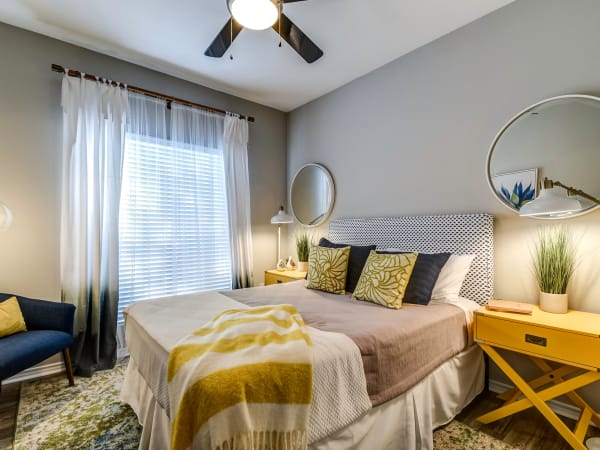 Well-decorated master bedroom with a ceiling fan in a model home at Azure Apartments in Corpus Christi, Texas