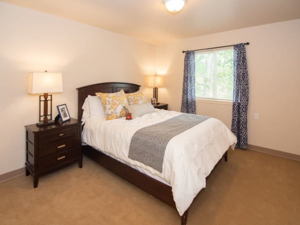 Spacious resident bedroom with a large window at Patriots Landing in DuPont, Washington.