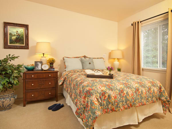 A resident bedroom with a nightstand at Patriots Glen in Bellevue, Washington.