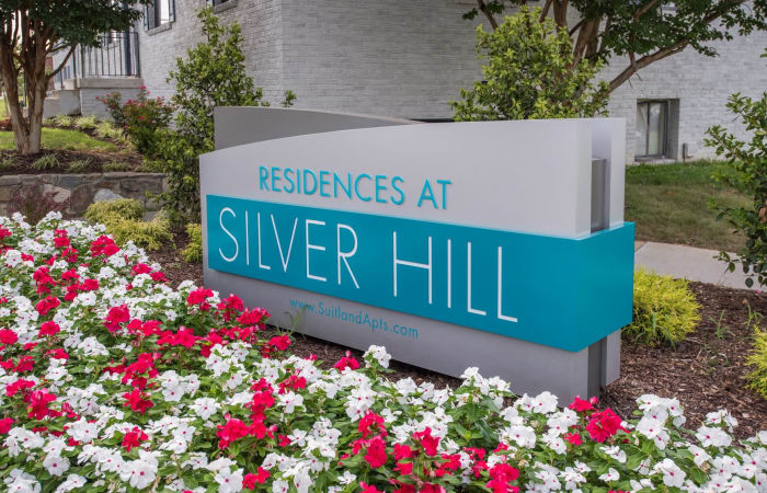 Sign surrounded by flowers outside The Residences at Silver Hill in Suitland, MD
