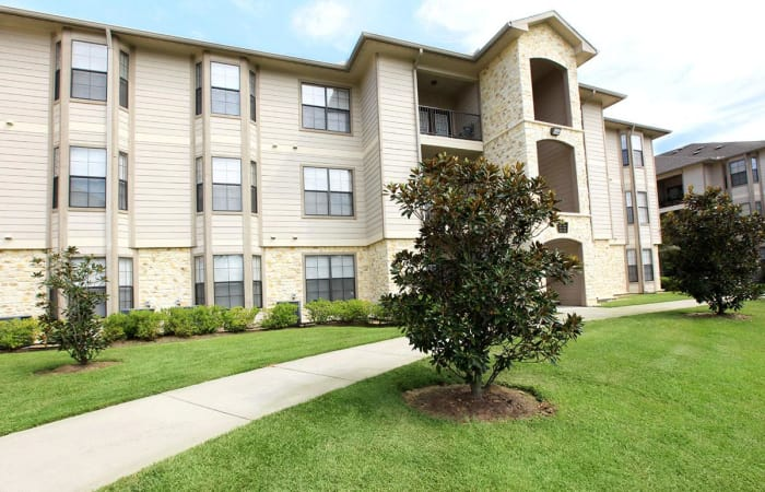 Walking path winding through green lawns in our community at Camden Lake Apartments in Baton Rouge, LA