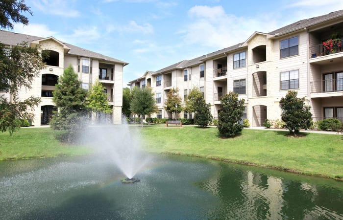 Well-maintained landscaping between resident buildings and onsite lake at Camden Lake Apartments in Baton Rouge, LA