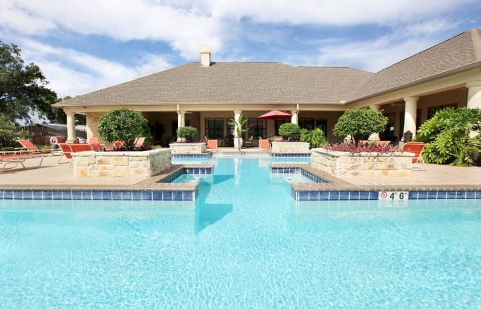 Swimming pool with resident clubhouse in the background at Camden Lake Apartments in Baton Rouge, LA