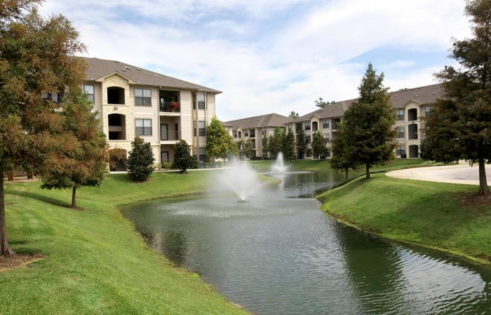 Community lake with fountain surrounded by green lawns at Camden Lake Apartments in Baton Rouge, LA