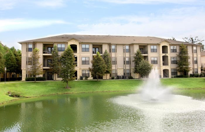 Resident buildings across lake with fountain at Camden Lake Apartments in Baton Rouge, LA