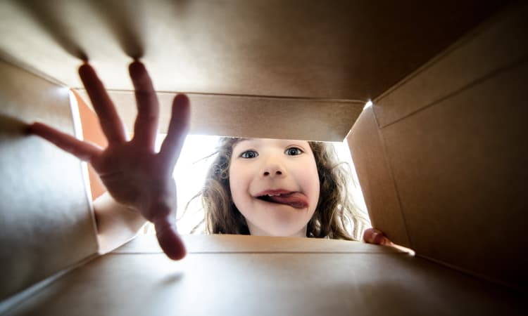 Child opening box at Squirrel Storage Waukee in Waukee
