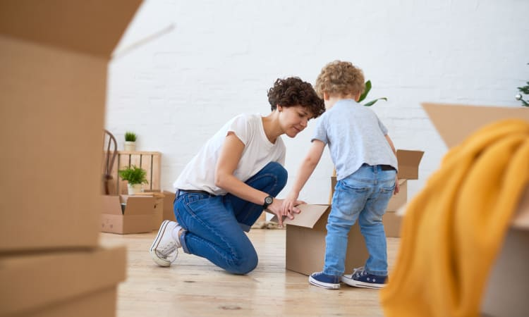 Child helping his mother with boxes to store at Granary Storage in Salt Lake City, Utah