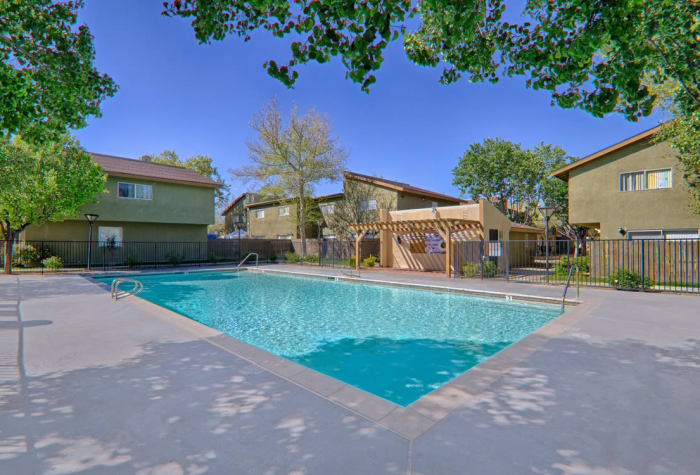 Beautiful, serene swimming pool on sunny day at Woodlands West Apartment Homes in Lancaster, CA