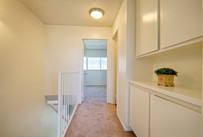 Upstairs hallway view in apartment home at Woodlands West Apartment Homes in Lancaster, CA