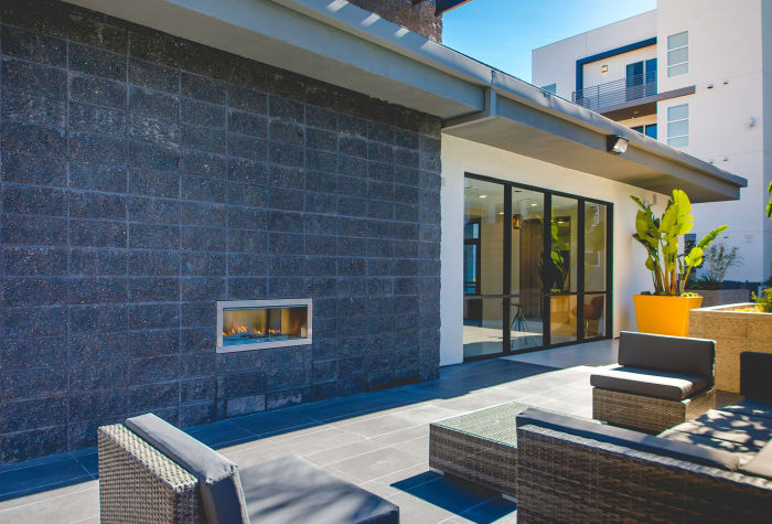 Fireplace and comfortable seating in outdoor lounge area at IMT Sherman Circle in Van Nuys, CA