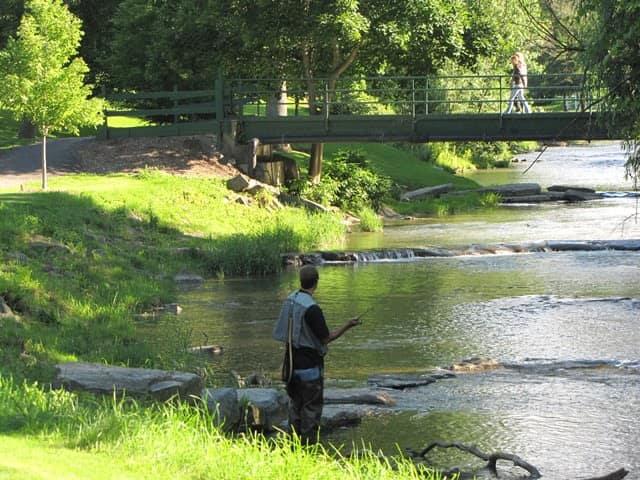 Person fishing in river at Braeside Apartments in Marcellus, NY
