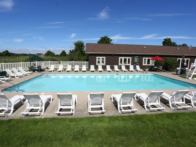 Long pool with seating arranged around it at Village Green Apartments