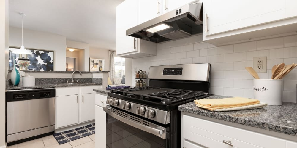 Modern kitchen with a subway tile backsplash and stainless-steel appliances in a model home at 200 East in Durham, North Carolina