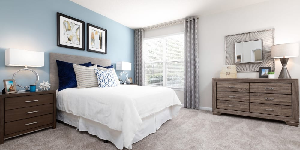 Well-furnished primary bedroom with an accent wall in a model apartment at 200 East in Durham, North Carolina