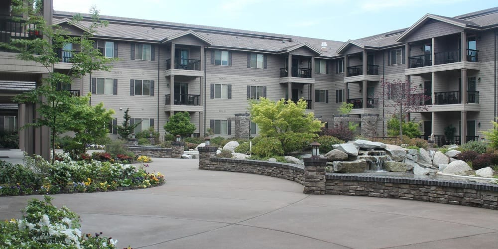 Inviting courtyard with a pond and lots of foliage at The Springs at Veranda Park in Medford, Oregon