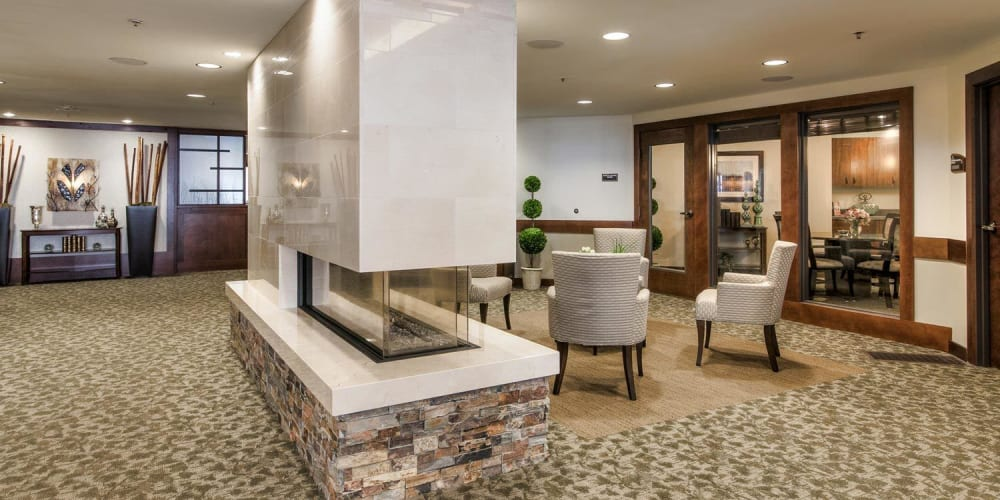 Inviting lounge with large modern block fireplace at The Springs at Carman Oaks in Lake Oswego, Oregon